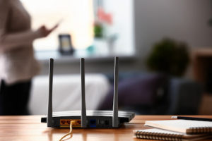 A router sits on a desk with notebooks and a pencil