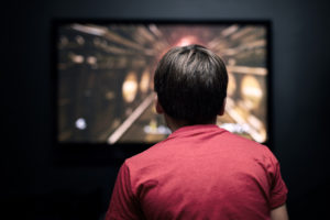 Boy sitting in front of 4K TV playing video game