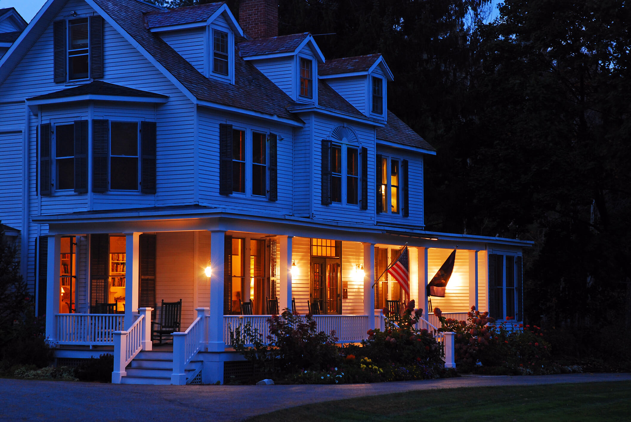 Large house at night with porch lit up
