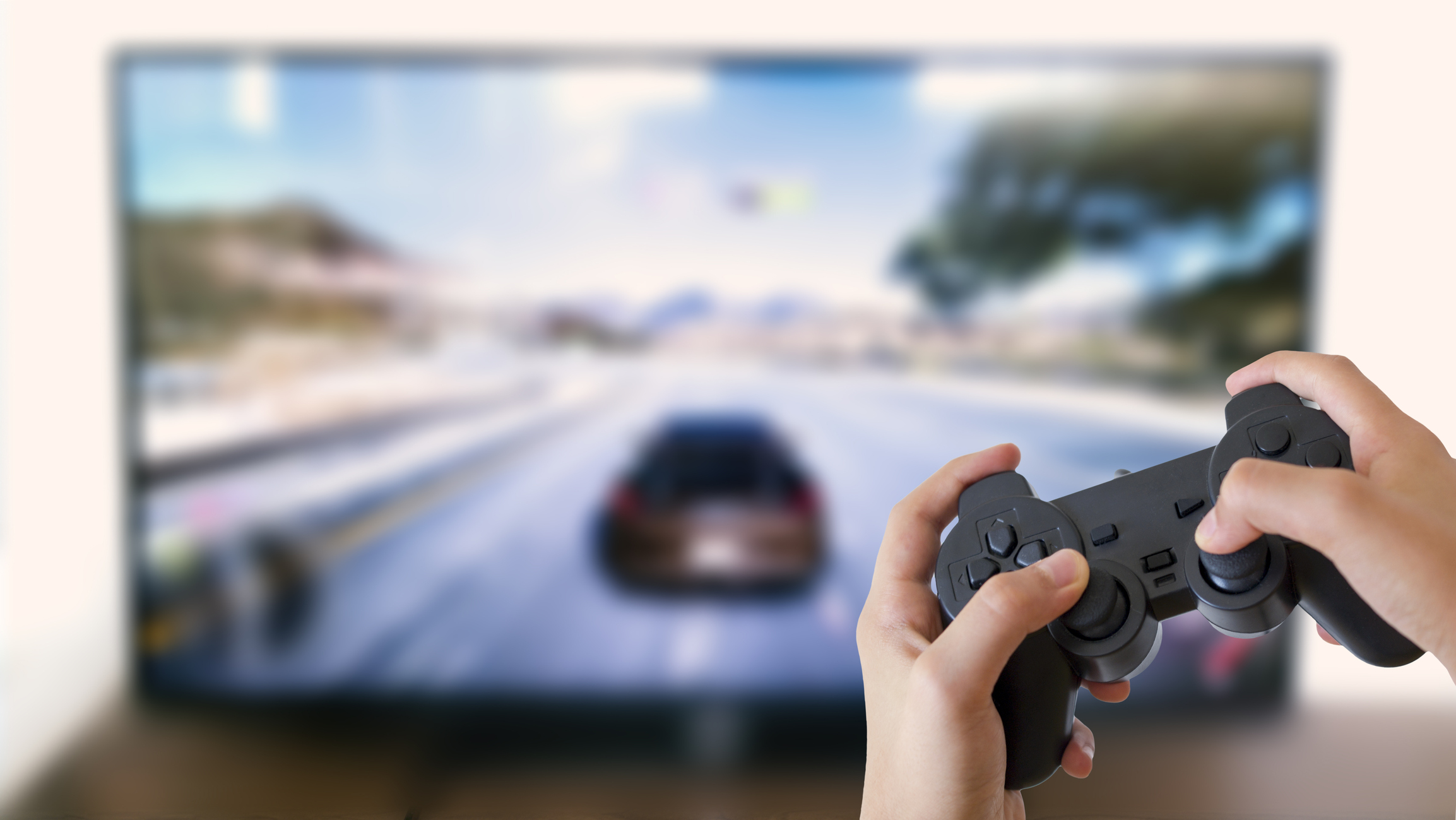 Boy holding game console with car racing game on 4K TV in background