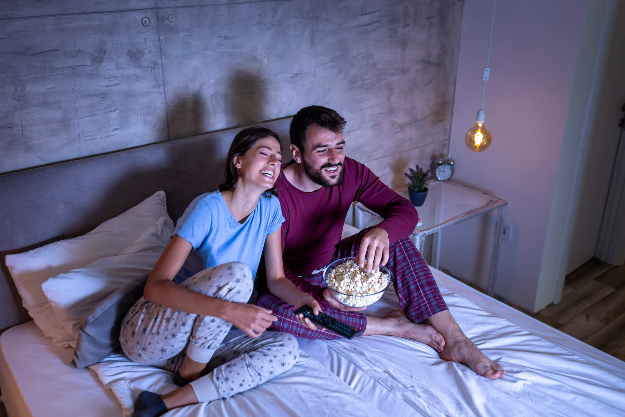 Couple watching streaming service on bed while snacking on popcorn