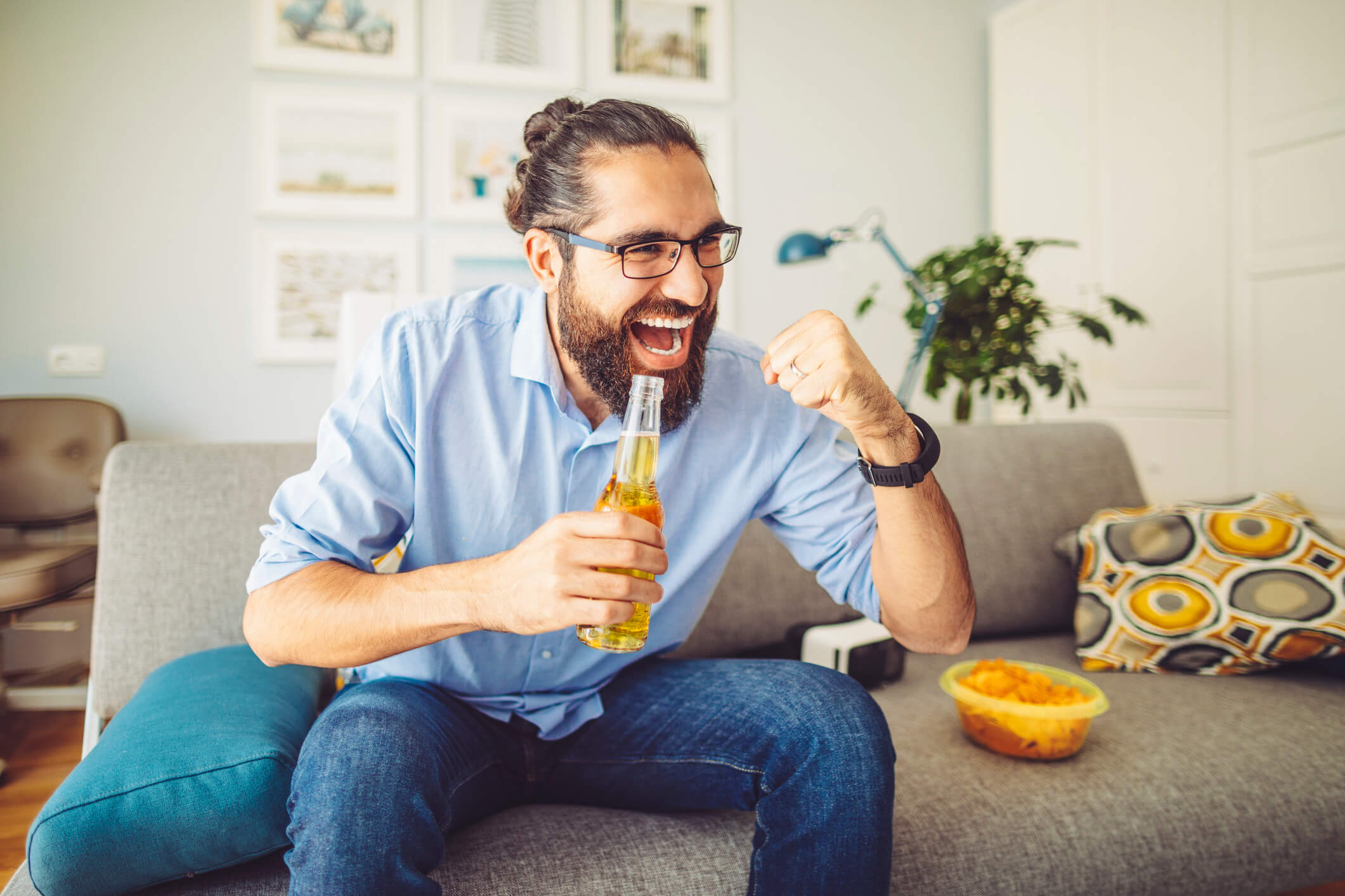 Man cheering on living room couch drinking beer and snacking on chips while watching The Draft