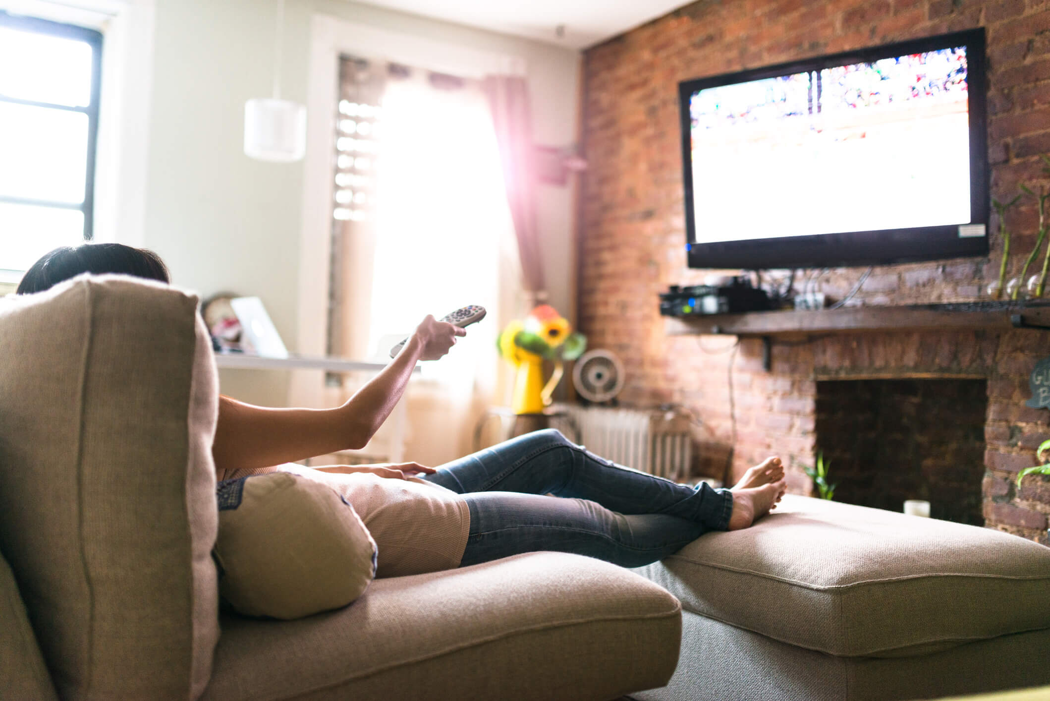 Woman relaxing on sofa setting up her smart TV