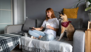 Woman watching streaming service on couch with dog while eating take out