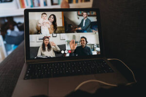 A laptop screen shows four family members on a Zoom video call