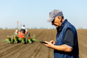 An older farmer looks at his tablet while another farmer plows a field in the background