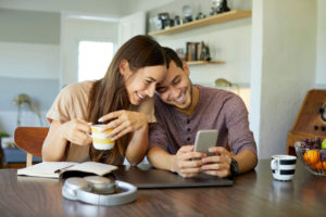 A young couple looks at a cell phone together.