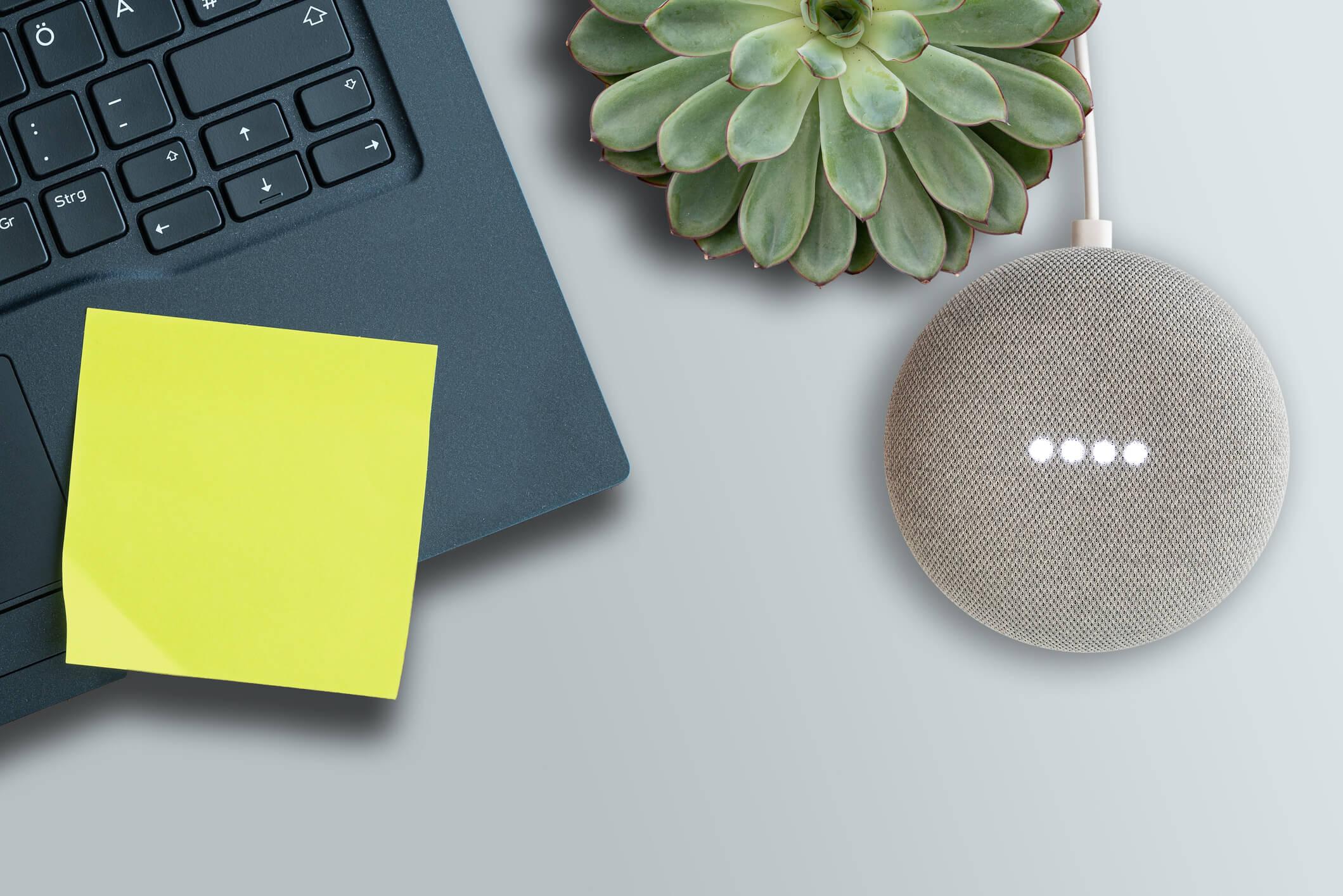 Google Home mini by a laptop