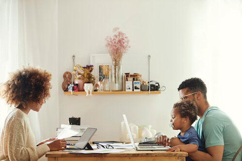 An African-American mom, dad, and son sit at opposite ends of a table while working online