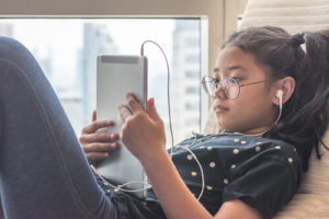 A young Asian girl listens to music on her tablet