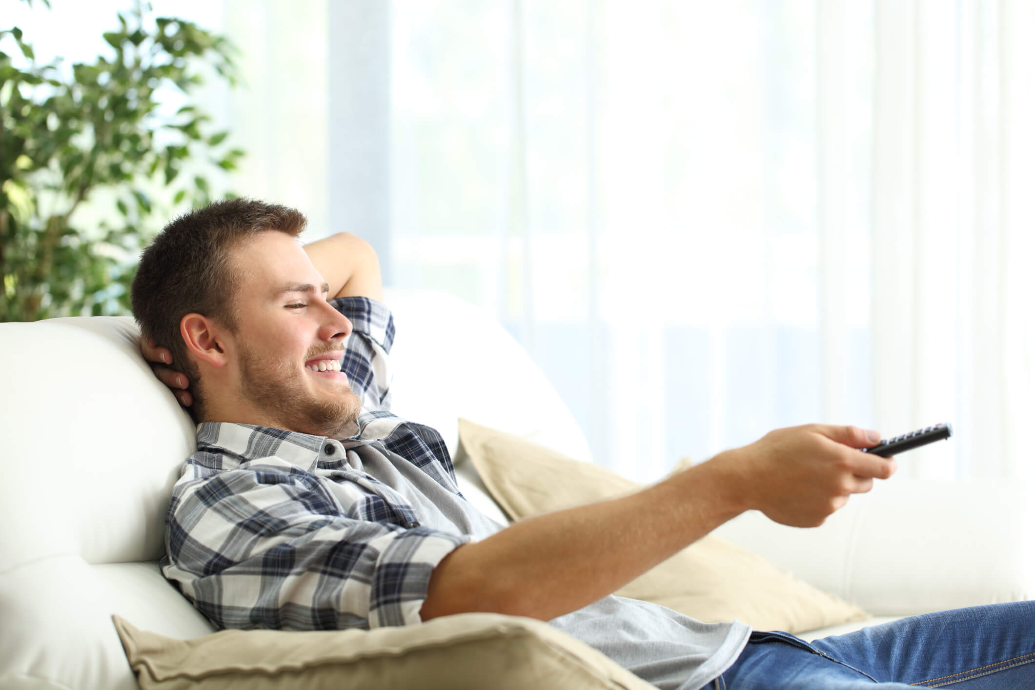 Happy man watching The Last Dance on couch in living room