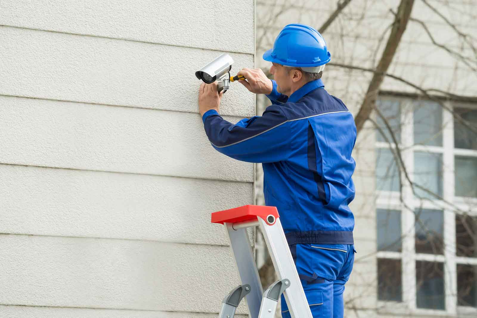 Male Technician Standing On Stepladder Fitting CCTV Camera