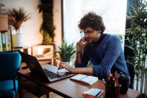 Man working on laptop using Surfshark VPN