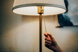 A hand pulling the pull chain on a lighted lamp