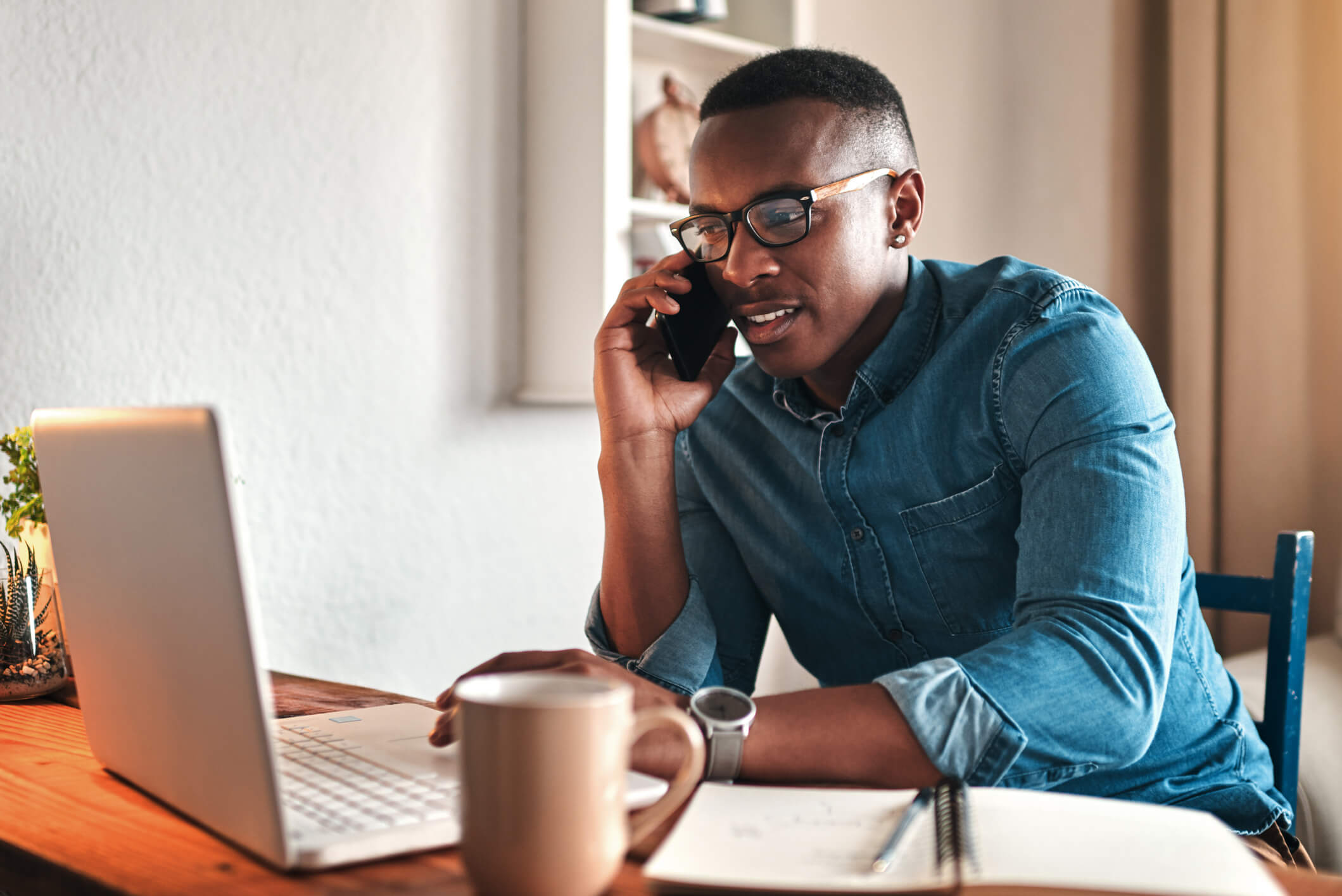 Man sitting at desk and calling Verizon customer service on his phone