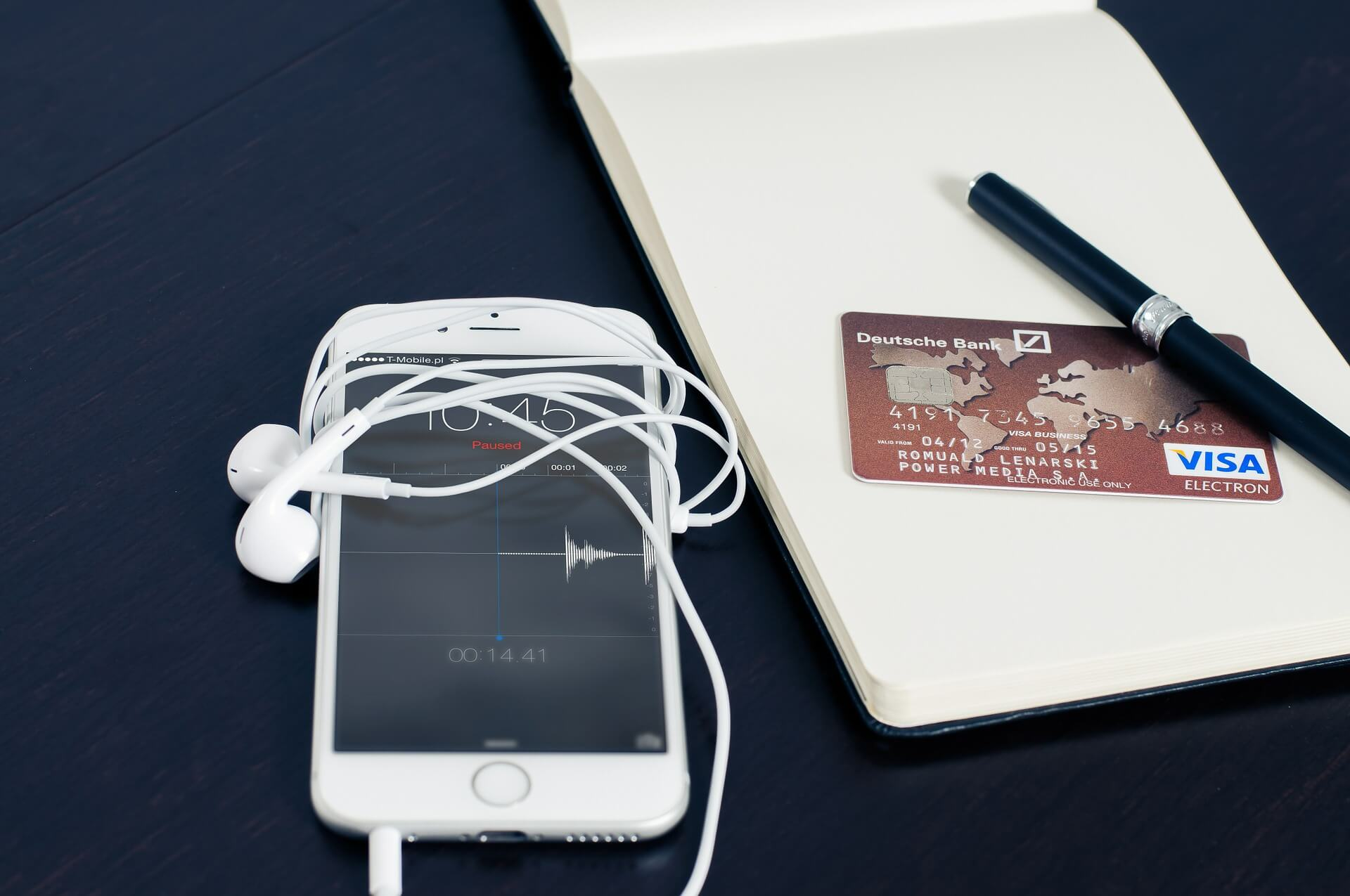 An iPhone sits on a table next to a credit card and a notepad.