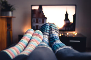 A couple's feet wearing cozy socks in front of a TV screen streaming a movie