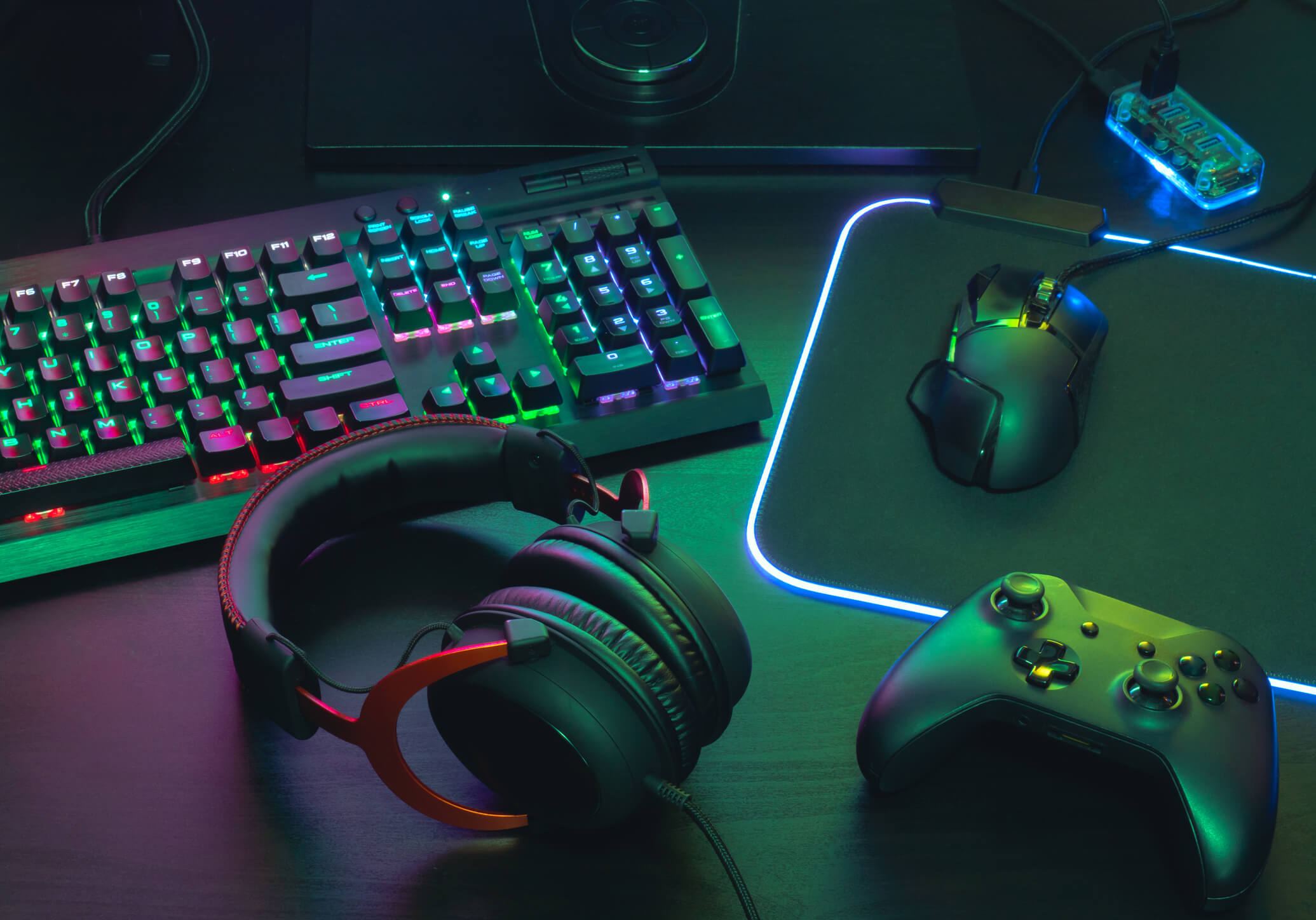 Gamer desktop setup with headphones, mouse, controller, and RGB keyboard and mousepad