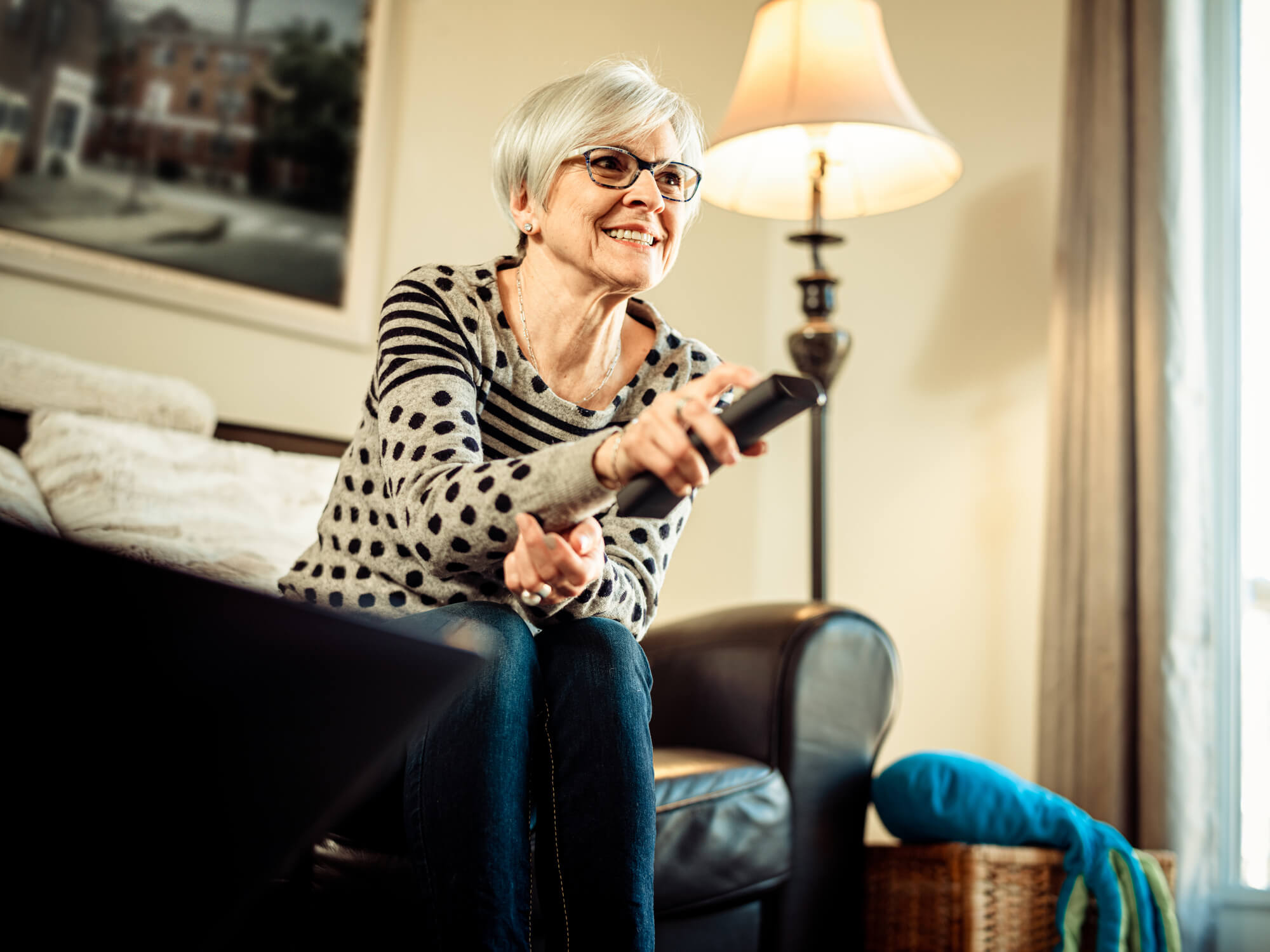 Grandmother sitting on couch in living room watching cable TV