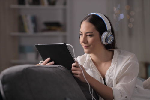 Woman watching streaming service on tablet with headphones on while sitting on couch
