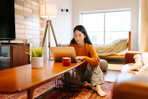 An Asian woman sits at a wooden table with her laptop
