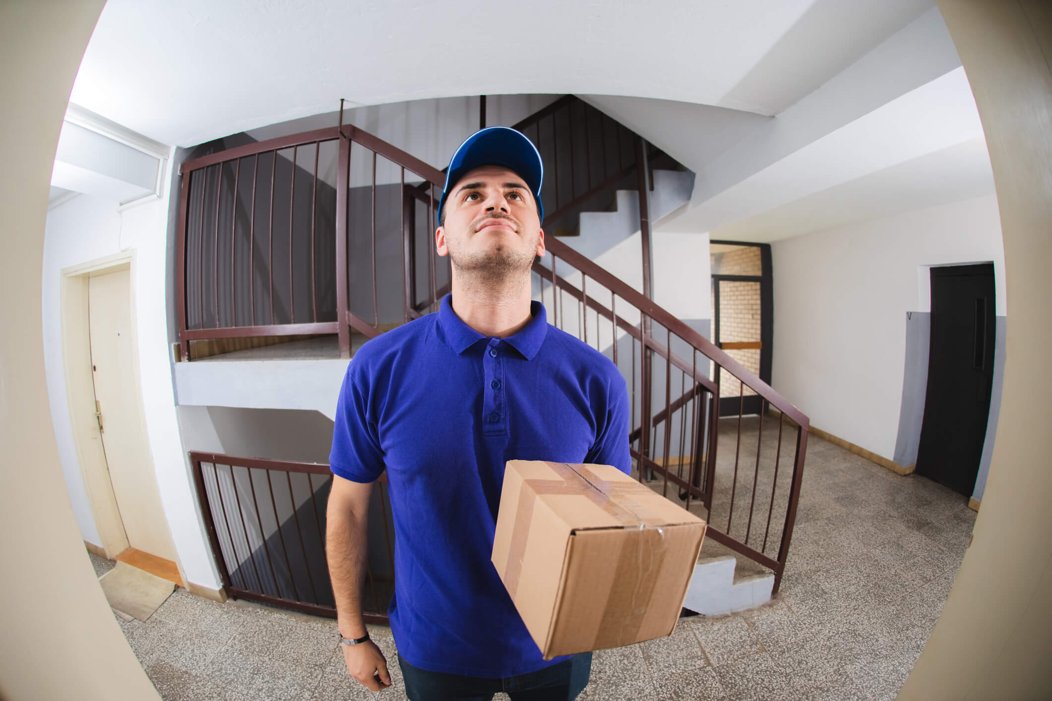 Man in a blue shirt seen through peephole standing holding package