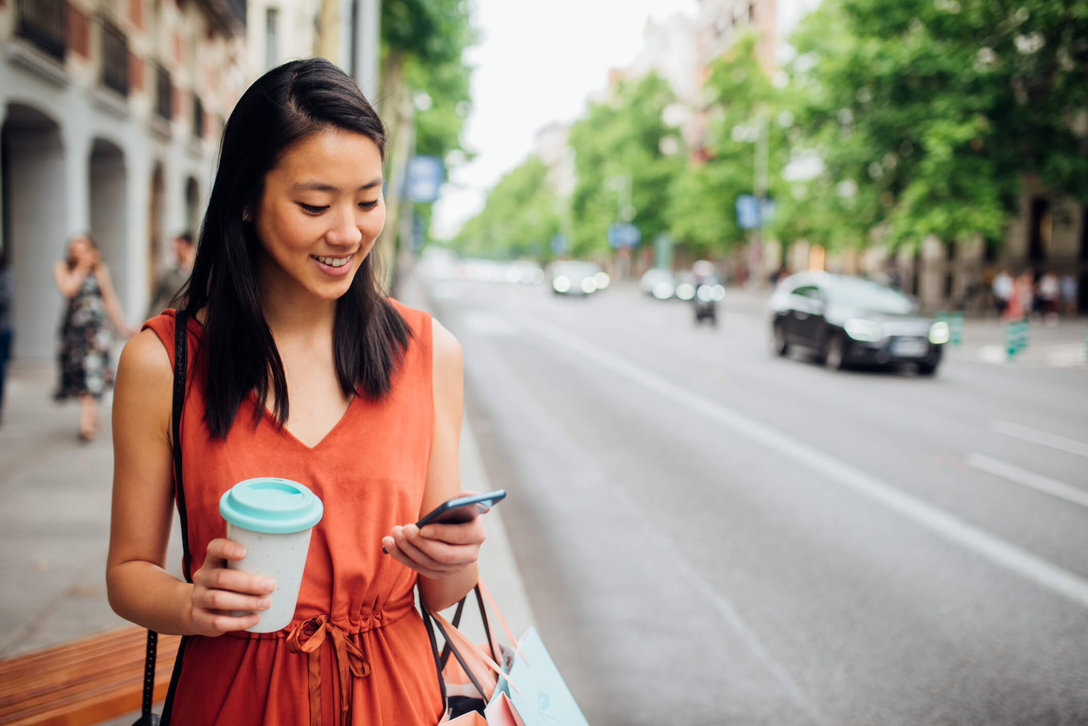 Woman holding a cup of coffee and her smartphone next to a city street