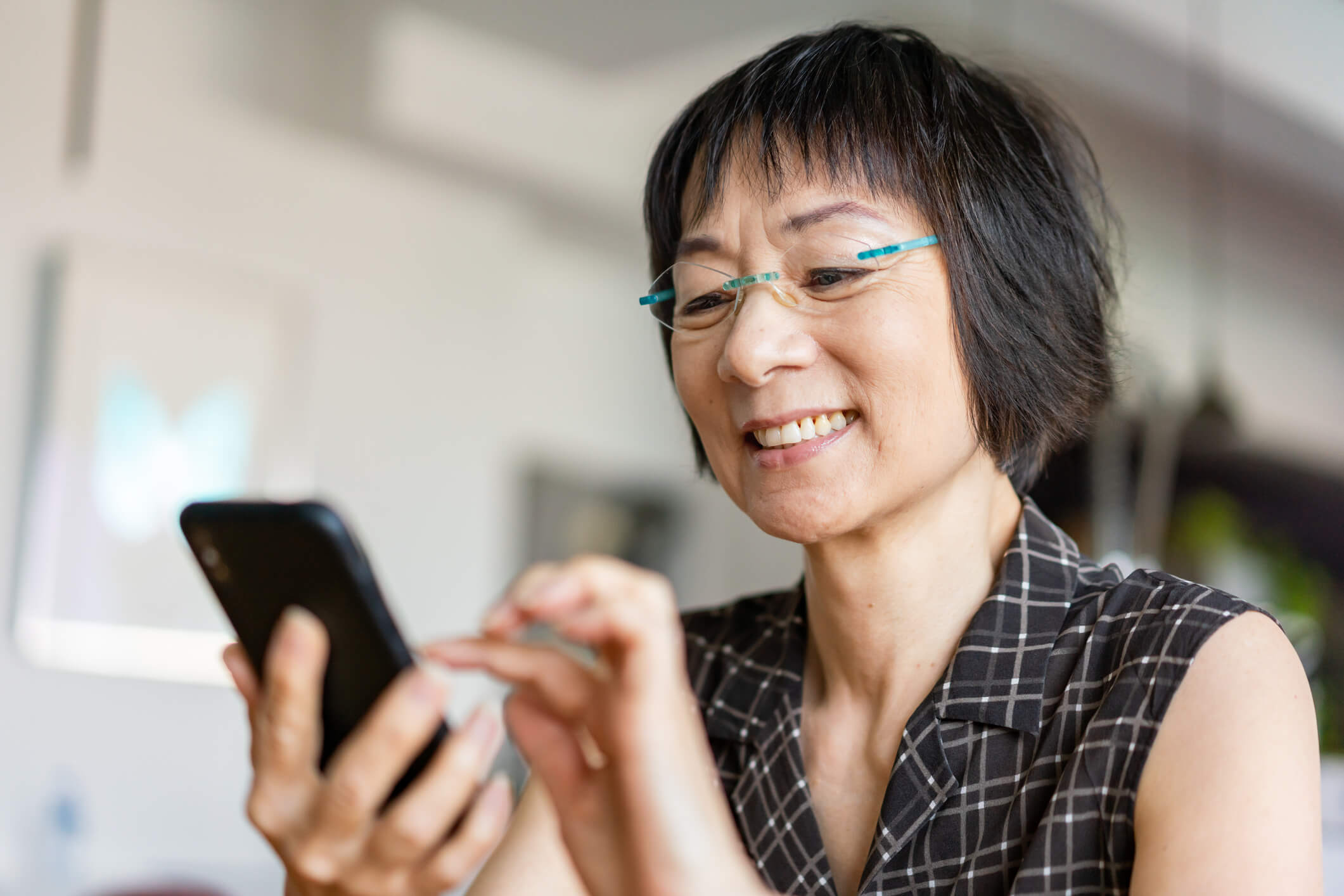 Senior age asian woman looks at a cell phone.