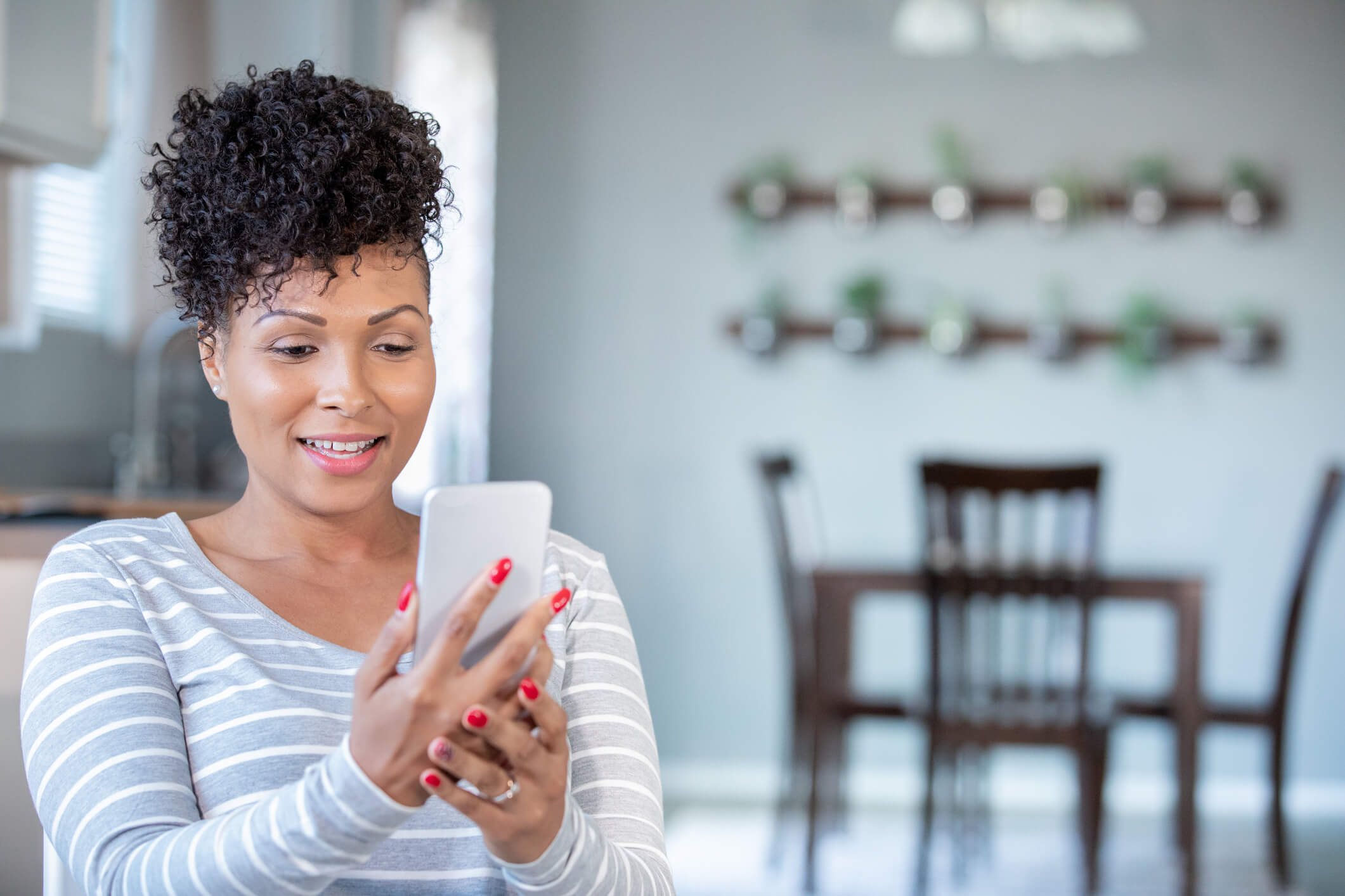 A woman sitting at home looks at her phone.