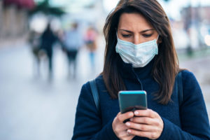 Woman using cell phone while wearing a mask.
