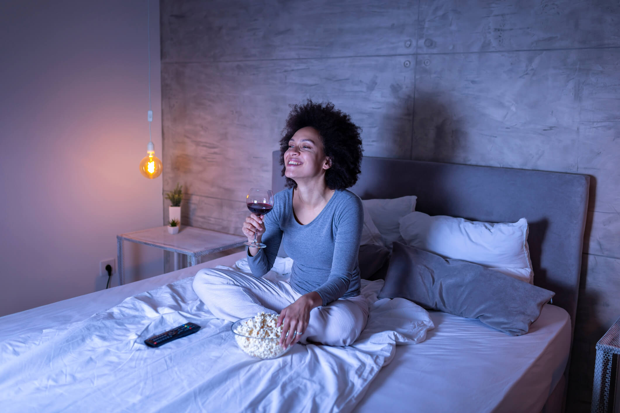 Woman sitting on bed eating popcorn and drinking wine while laughing at movie on TV