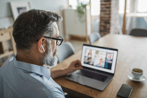 A middle-aged man listens to a Zoom video meeting on his laptop