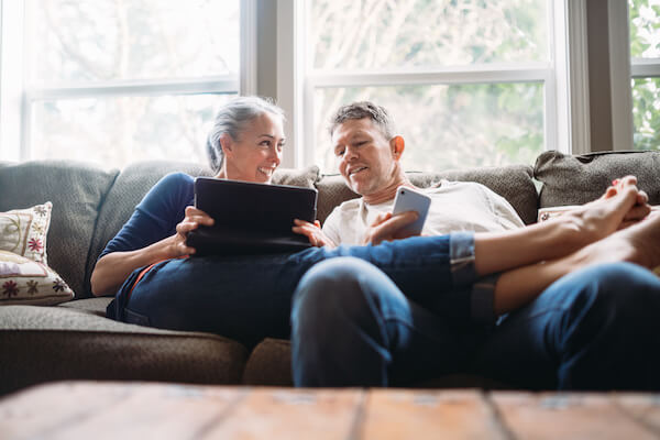 An older White man and woman lounge on a couch with their tablet and cell phone