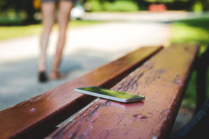 Woman forgetting her phone on a park bench