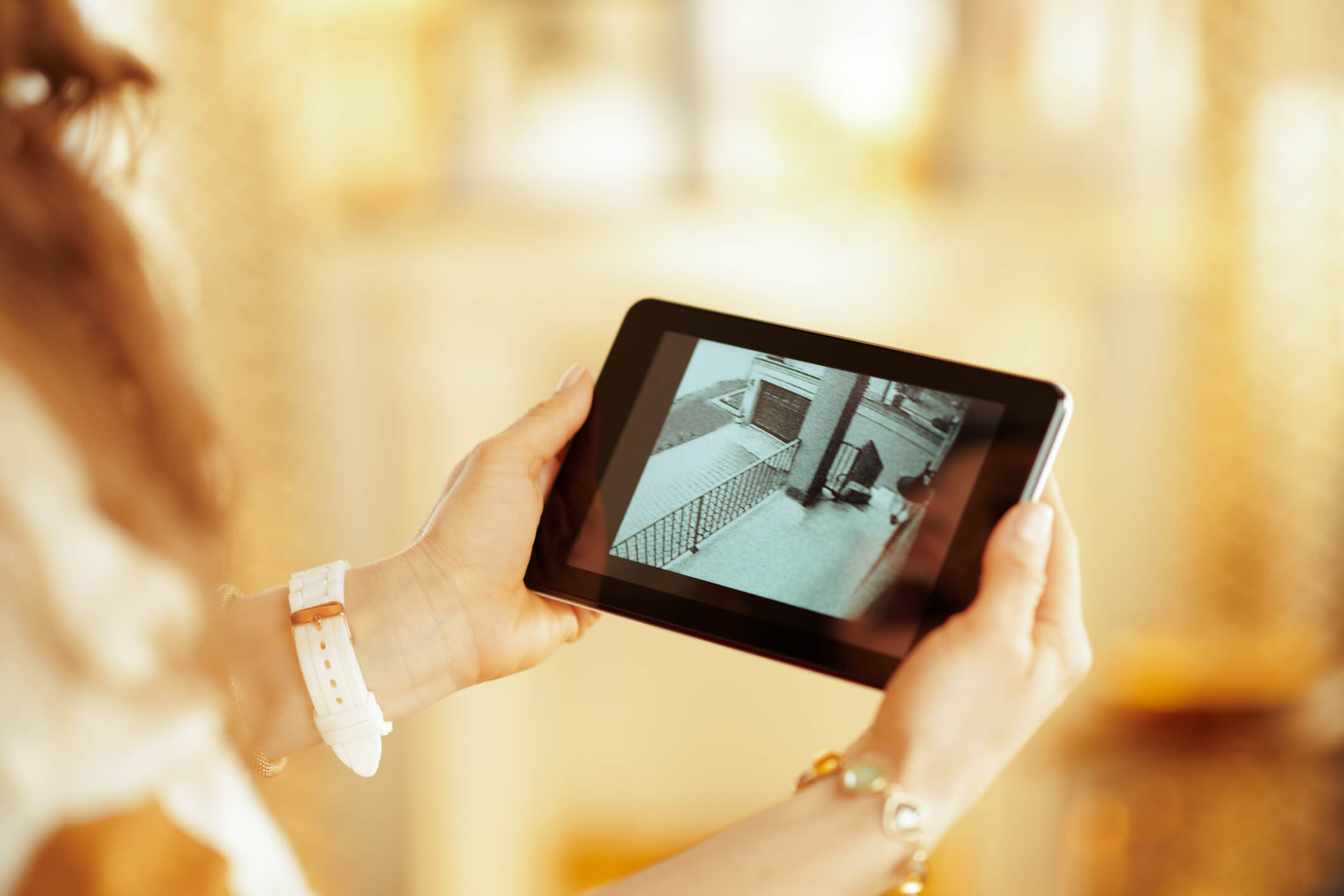 Person holding a tablet displaying a security camera feed