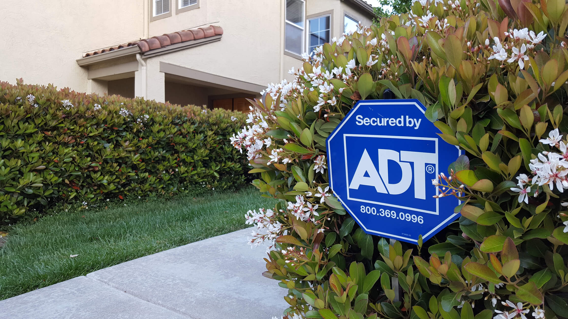 ADT sign in a bush near a driveway