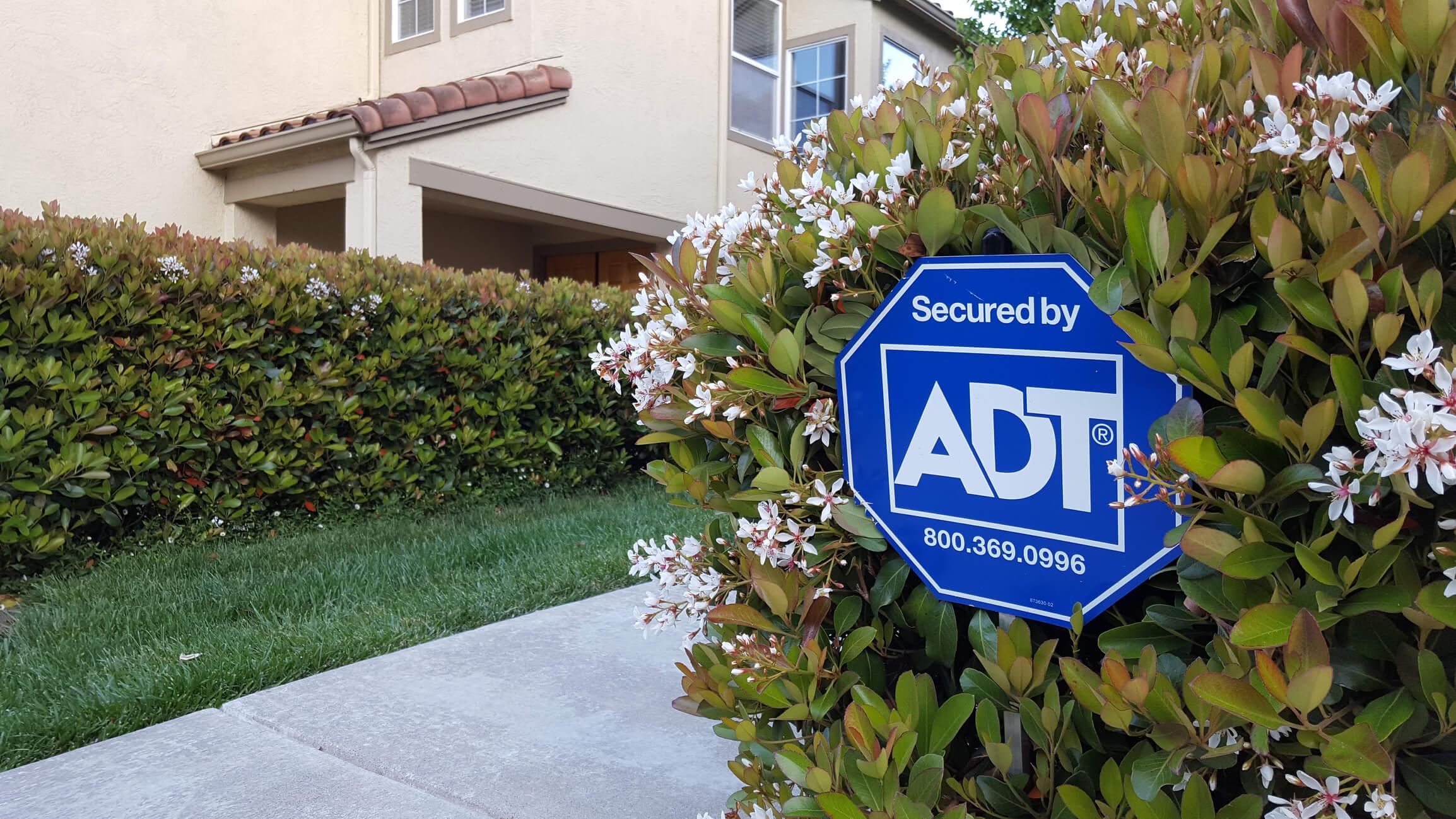ADT sign in a bush near a driveway