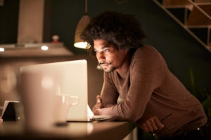 A Black man looks at his laptop while working late into the night