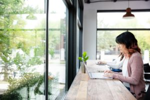 Woman using laptop public space - bets vpn for windows