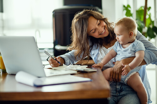 A woman holds her infant in her lap while she works on her laptop