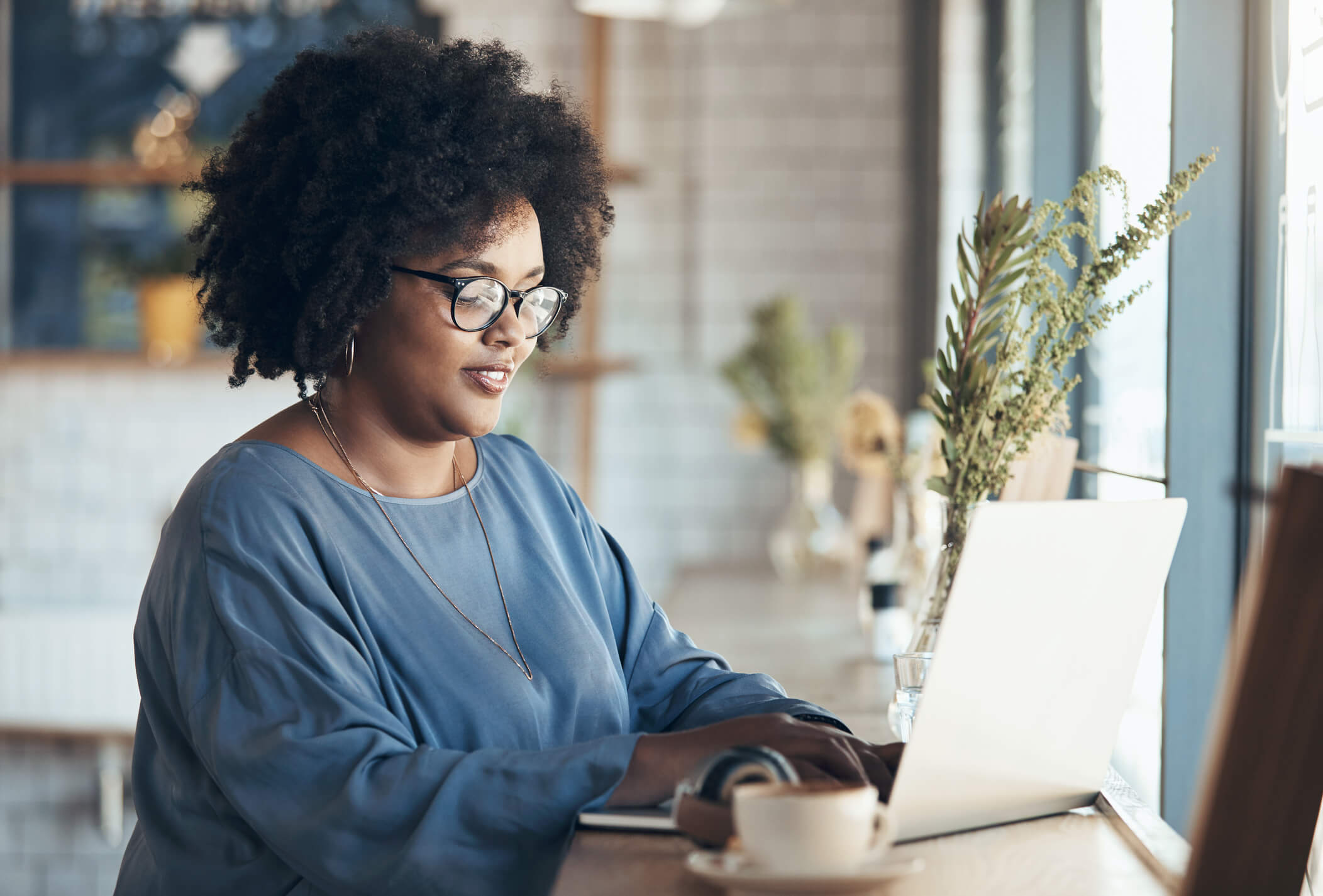 Woman on laptop comparing IPVanish and Norton Secure VPN