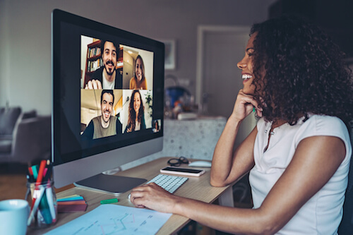 A woman sits at her desk and videoconferences with four teammates