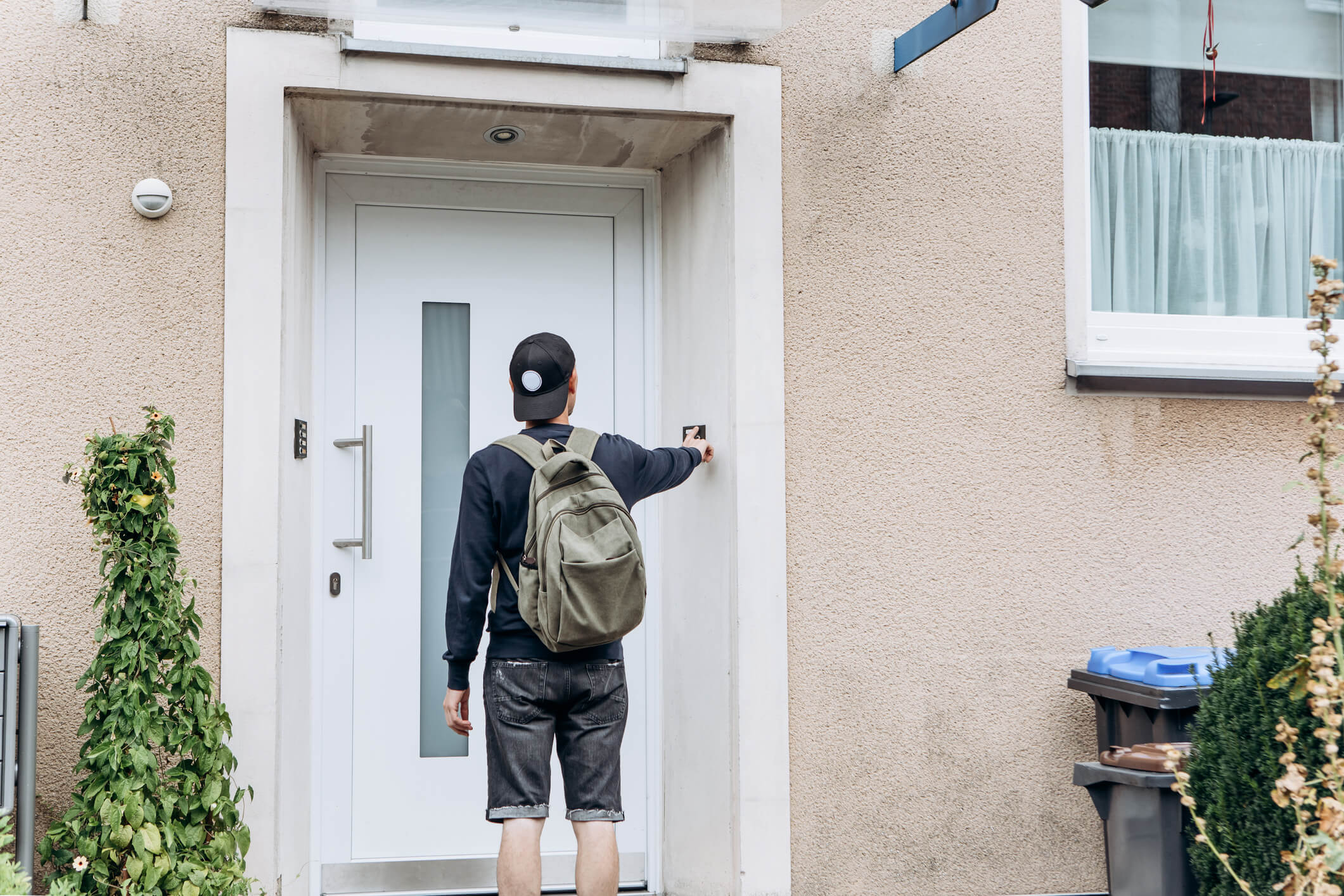 Person with baseball cap and backpack rings a doorbell