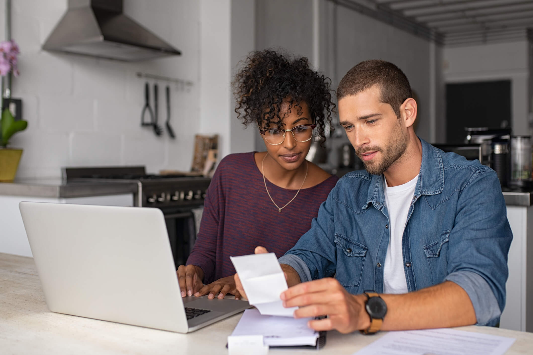 a couple looks at paperwork in front of a laptop