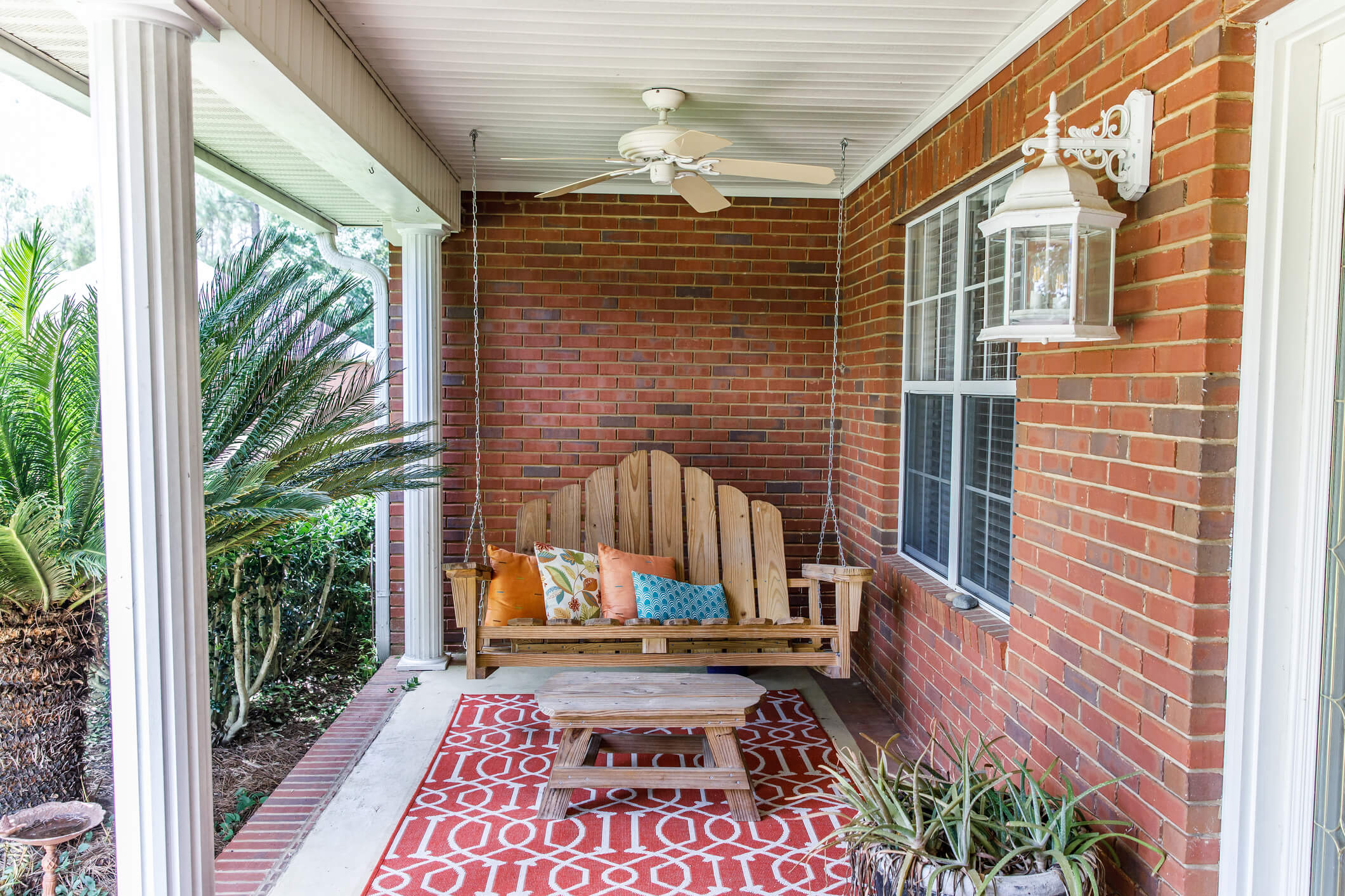 View of leisurely front porch with wooden bench, rug, and coffee tables