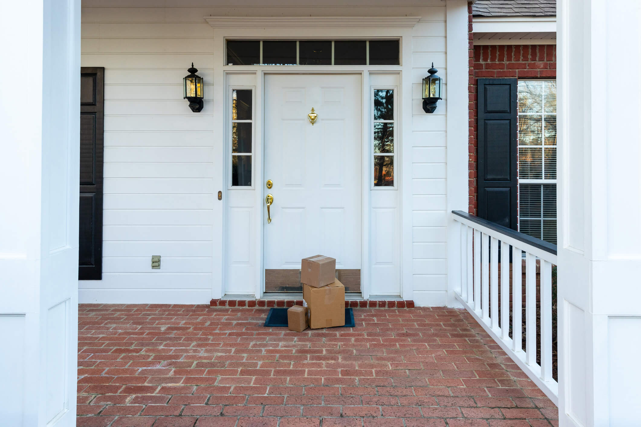 Three boxes piled in front of a white front door on a red brick porch