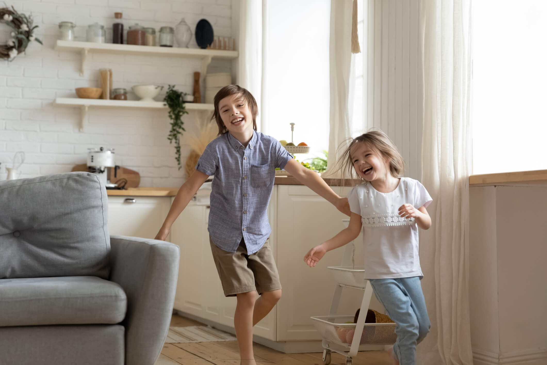 Two children smiling while running through a living room