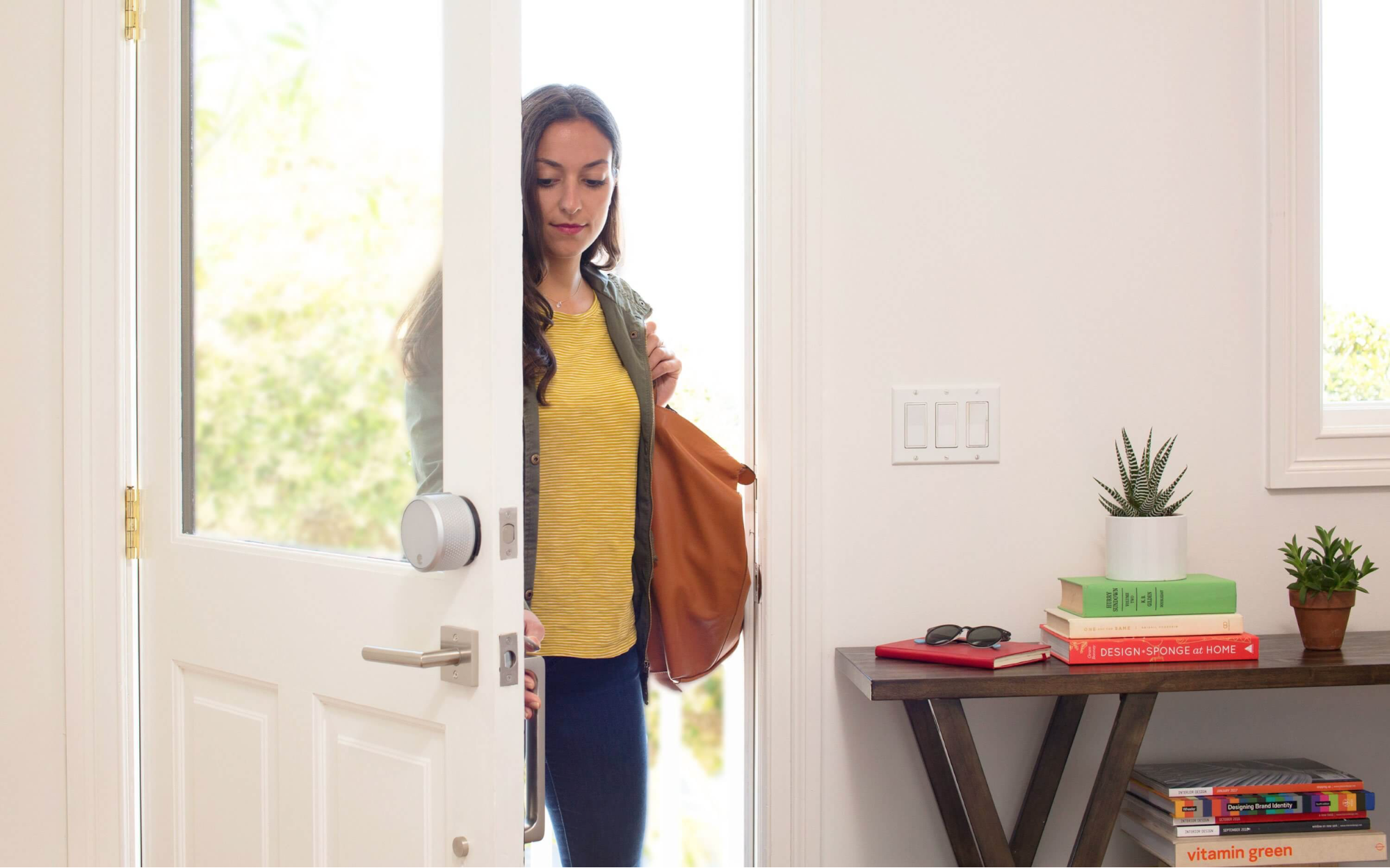 Woman entering through a door with an August Smart Lock Pro installed