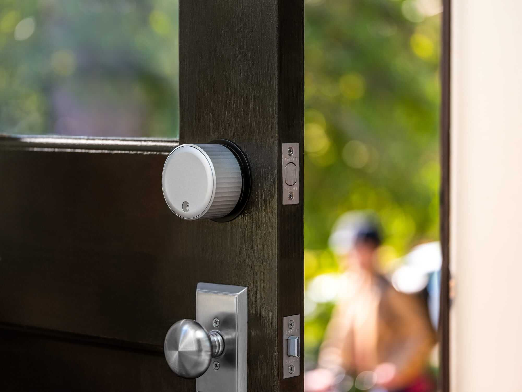 August Wi-Fi Smart Lock on a front door that is partially open showing a blurred person in the background