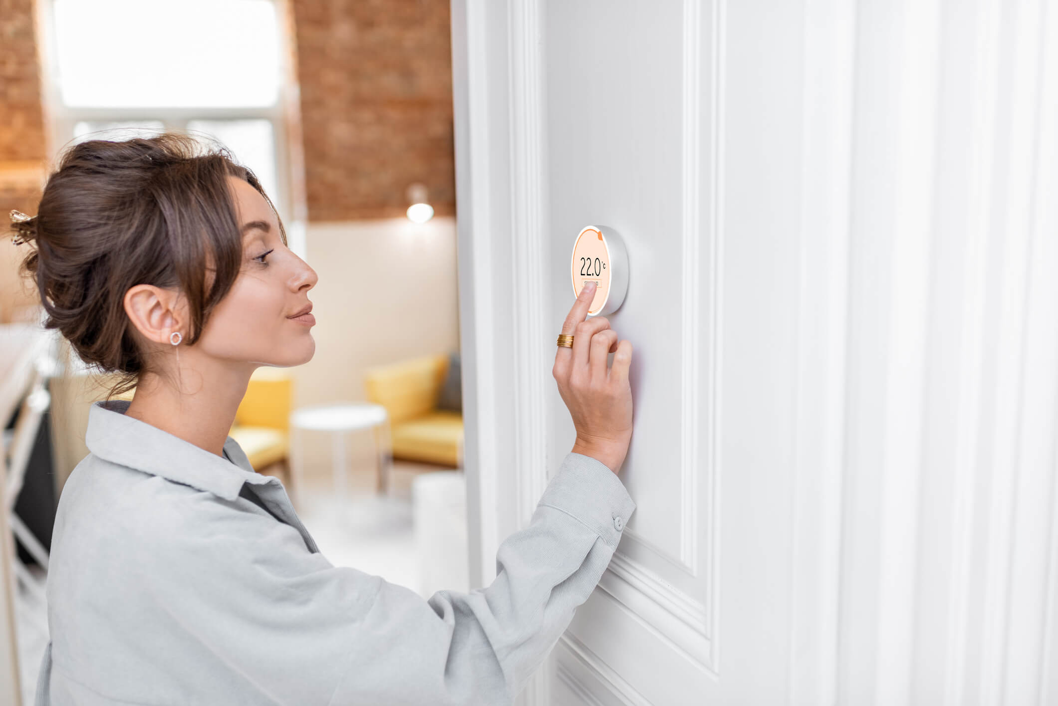 Woman adjusting Nest thermostat E